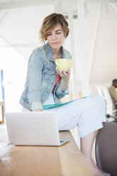 Office worker with coffee using laptop - CAIF13770