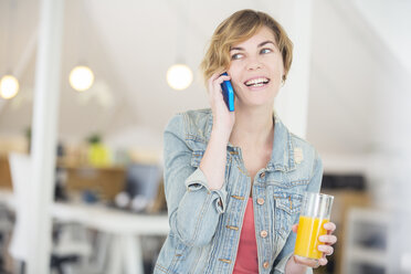 Office worker talking on phone and holding glass of juice - CAIF13773