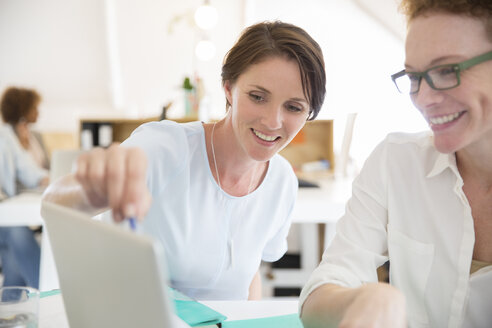 Women using laptop in office and smiling - CAIF13803