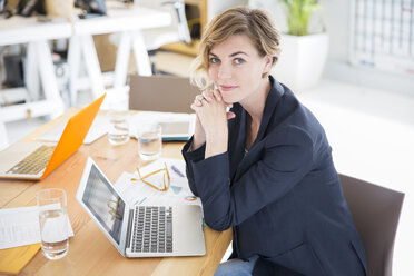 Portrait of woman sitting at desk with laptop in office - CAIF13809