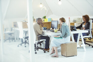 Office workers talking at desk - CAIF13827