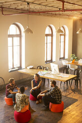 Creative business people talking in circle in office - CAIF13854