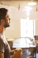 Pensive casual businessman reviewing hanging diagrams in office - CAIF13863