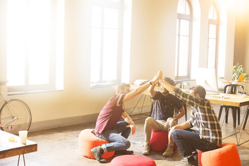 Creative business people joining hands in circle in sunny office - CAIF13866