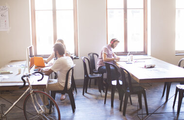 Creative business people working at tables in sunny office - CAIF13869