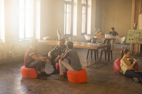 Casual business people meeting in circle in sunny office - CAIF13875