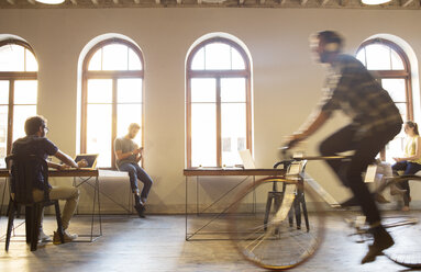 Casual businessman riding bicycle in open office - CAIF13896