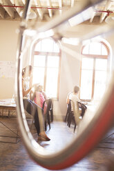 Creative business people working behind bicycle wheel in office - CAIF13917