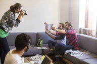 Creative businessmen with proofs posing for coworker with instant camera - CAIF13926