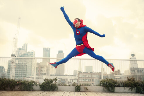 Superhero jumping on city rooftop - CAIF13929