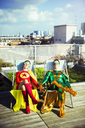 Superhero couple sitting on city rooftop - CAIF13935