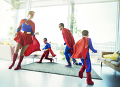 Superhero family chasing each other in living room - CAIF13941