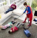 Superhero vacuuming around family in living room - CAIF13944