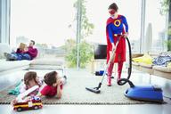 Superhero vacuuming around family in living room - CAIF13947