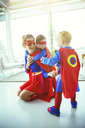 Superhero mother and children playing in living room - CAIF13950