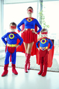 Superhero mother and children standing in living room - CAIF13953