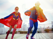 Superheroes running on city rooftop - CAIF13959