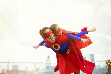 Superhero mother and daughter playing on city rooftop - CAIF13968