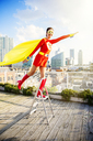 Superhero standing on stepladder on city rooftop - CAIF13971