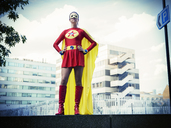 Superhero standing with hands on hips in city - CAIF13974
