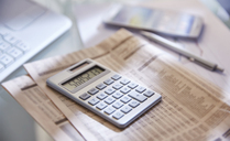 Calculator,close up,newspaper and pen on desk - CAIF13989