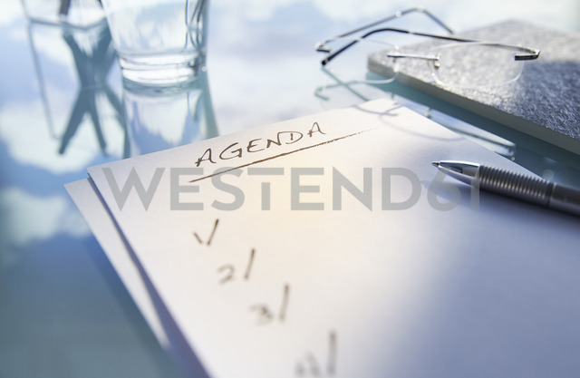 Close up of desk with,glass,glasses and note saying 'agenda',pen - CAIF14013