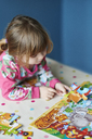 Girl assembling jigsaw puzzle - CAIF14037