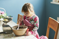 Curious girl baking with mixing bowl in kitchen - CAIF14043