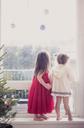 Girls on window ledge below Christmas ornaments - CAIF14049