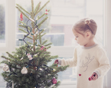 Girl decorating small Christmas tree - CAIF14061