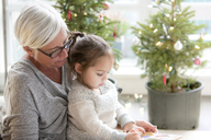 Grandmother watching granddaughter drawing in front of Christmas trees - CAIF14064