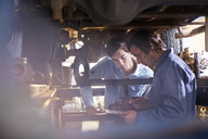 Mechanic and customer under car in auto repair shop - CAIF14067