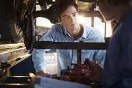 Mechanic and customer talking under car in auto repair shop - CAIF14073