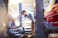 Mechanics discussing engine part in auto repair shop - CAIF14076