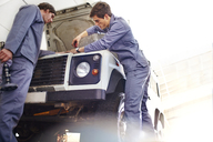Mechanics working on engine in auto repair shop - CAIF14079