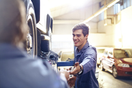 Mechanic reaching for tool in auto repair shop - CAIF14082