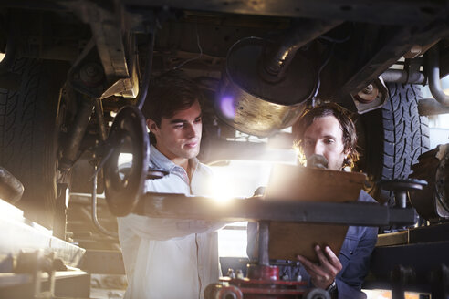 Mechanics with clipboard under car in auto repair shop - CAIF14088