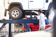 Mechanic under car talking to customer in auto repair shop - CAIF14091