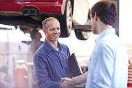 Mechanic and customer handshaking in auto repair shop - CAIF14094