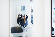 Customer with long hair looking into mirror in hair salon - CAIF14103