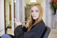 Portrait woman texting with cell phone in hair salon - CAIF14106