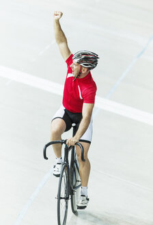 Track cyclist celebrating in velodrome - CAIF14124