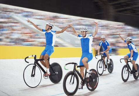 Track cycling team celebrating in velodrome - CAIF14127