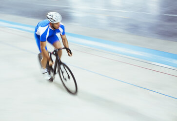 Track cyclist riding in velodrome - CAIF14145
