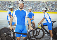 Track cyclists standing in velodrome - CAIF14154