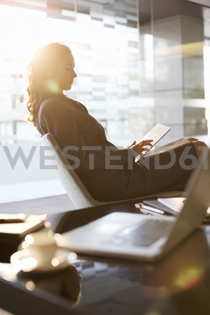 Businesswoman using digital tablet in office - CAIF14190