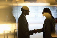 Businessman and businesswoman handshaking in lobby - CAIF14193