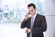 Smiling businessman talking on cell phone and looking at wristwatch - CAIF14208