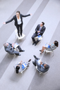 High angle view of businesswoman standing on chair in circle with co-workers - CAIF14241
