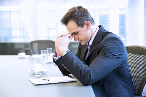 Businessman with head in hands in conference room - CAIF14250
